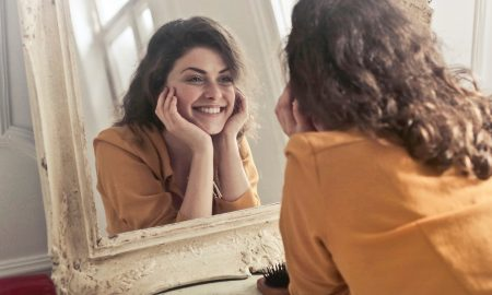 woman looking in the mirror smiling